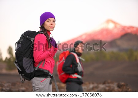 Hiking people on mountain. Hiker couple walking with backpack in high altitude mountains. Young woman hiker in focus trekking at sunset Tenerife, Canary Islands, Spain. - stock photo