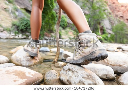 Hiking shoes on hiker outdoors walking crossing river creek. Woman on hike trekking in nature. Close up of female hiking boots in action. - stock photo