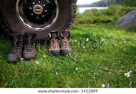 Hiking shoes set by truck tire, Ozetta Lake, Olympic National Park, WA - stock photo