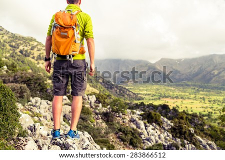 Hiking tourist man looking at beautiful mountains inspirational landscape. Hiker trekking with backpack on rocky trail footpath. Healthy fitness lifestyle outdoors concept on Crete Greece