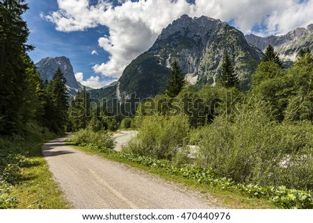 Hiking trail and river in front of mountains panorama