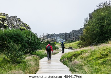 Hiking trail in Iceland, backpacker walking in rocky canyon, cloudy summer. Beautiful icelandic landscape.