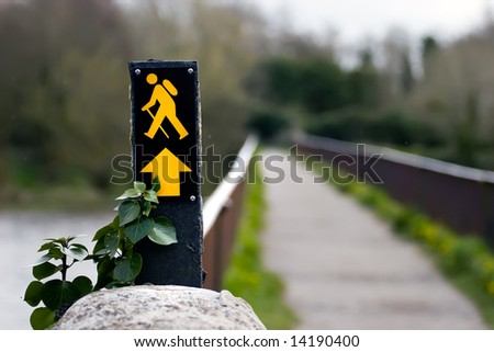 Hiking/trekking sign with out of focus food bridge in background in landscape view. - stock photo
