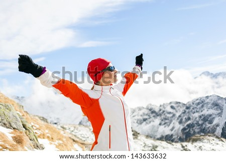 Hiking woman and success in mountains, arms outstretched. Female fitness and healthy lifestyle outdoors in winter nature on trail mountain ridge - stock photo