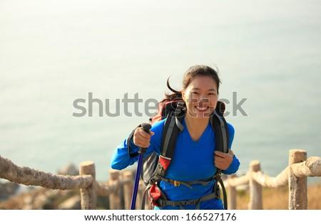 hiking woman climbing mountain seaside - stock photo