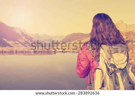 Hiking woman enjoying the Swiss alps landscape - stock photo