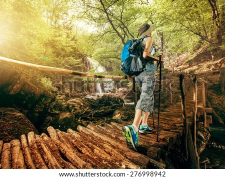 Hiking. Woman hikers walking on a bridge on the forest in the mountains on the waterfall. Girl with a backpack and sneakers traveling outdoors. Adventure in a hike. - stock photo