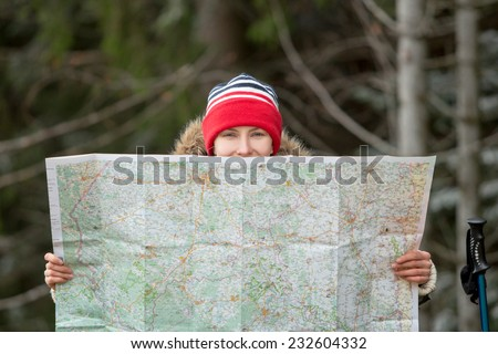 Hiking woman in autumn or winter nature holding map outdoors over dark forest. daylight focus on face - stock photo
