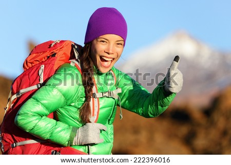 Hiking woman in winter jacket giving thumbs up smiling. Young Asian woman hiker smiling joyful at camera outdoor on hike trip. Beautiful young mixed race Asian Chinese / Caucasian woman in mountain. - stock photo