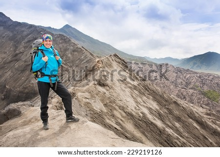 Hiking woman on top happy and celebrating success. Female hiker on top of the world cheering in winning gesture having reached summit of mountain