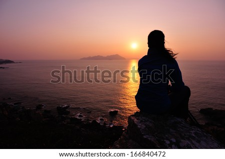 hiking woman sit on mountain rock watching the sunrise at the sea - stock photo