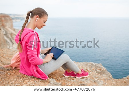 hiking woman sitting on seaside rock and use digital tablet. Young happy sporty woman sitting on rock by sea. sea view. healthy way of life. sports outdoor