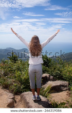 hiking woman stand seaside rock looking the view with arms open - stock photo