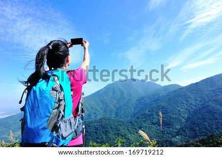hiking woman taking photo with smart phone at mountain peak  - stock photo
