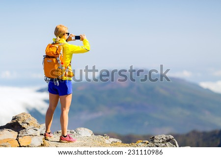 Hiking woman taking pictures in mountains with smart phone. Fitness and healthy lifestyle outdoors in summer nature on La Palma, Canary Islands. Using smartphone outdoor. - stock photo