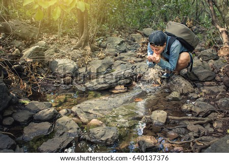 hiking Woman thirsty and taking clear water at small stream by hands for drink