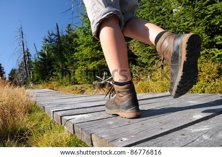 Hiking woman with boots on wooden trail - stock photo