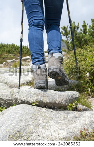 Hiking woman with trekking boots and sticks on the rocky trail. Active and healthy lifestyle.