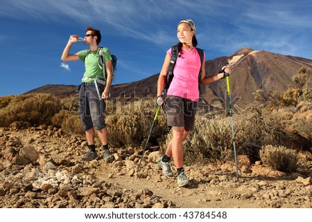 Hiking. Young couple hiking / backpacking in very scenic and beautiful volcanic landscape on the volcano, Teide, Tenerife, Spain. - stock photo