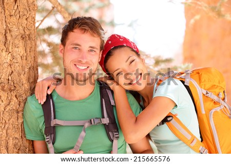 Hiking young couple portrait of happy hikers in Bryce Canyon walking smiling happy together. Multiracial couple, young Asian woman and Caucasian man in love, Bryce Canyon National Park landscape, Utah - stock photo