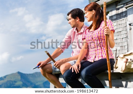 Hiking - Young couple sitting at mountain hut in the Bavarian Alps and enjoys the panorama in the leisure time or in vacation - stock photo