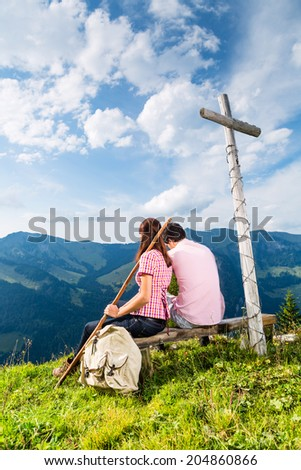Hiking - Young couple sitting on mountain summit at cross in the Bavarian Alps and enjoys the panorama in the leisure time or in vacation