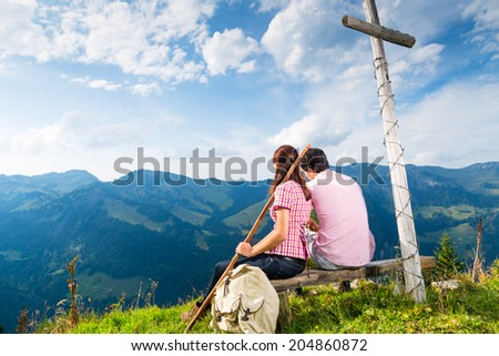 Hiking - Young couple sitting on mountain summit at cross in the Bavarian Alps and enjoys the panorama in the leisure time or in vacation - stock photo