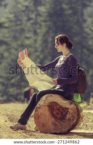 Hiking young lady resting on a stump and reading a travel map on a sunny day. - stock photo