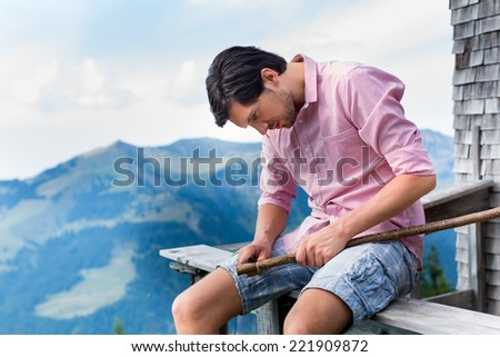 Hiking - Young man sitting at mountain hut in the Bavarian Alps and enjoys the panorama in the leisure time or in vacation, he carves a stick - stock photo