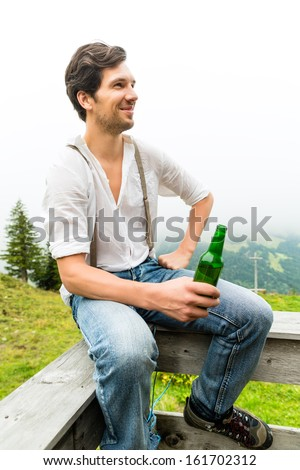 Hiking - Young man sitting at mountain hut with beer bottle in the Bavarian Alps enjoying the panorama in the leisure time or in vacation - stock photo