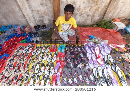 HIKKADUWA, SRI LANKA - FEBRUARY 23, 2014: Young local market vendor selling sandals. The Sunday market is great way to see local life come alive along with fresh produce and local delicacy - stock photo