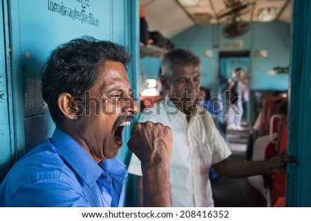 HIKKADUWA, SRI LANKA - MARCH 12, 2014: Local man yawning in train. Trains are very cheap and poorly maintained but it's the best option to witness a bit of everyday local life. - stock photo