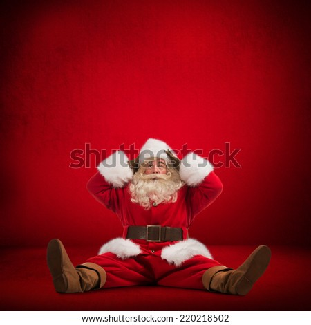 Hilarious and funny Santa Claus sitting on floor and looks frustrated on a red background full length - stock photo