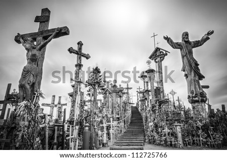 Hill of crosses in Siauliai, the city of Lithuania. Old stairway goes to gray sky. Stairs lead to the top of hill. Crosses and statues of saints near. Sun shines weakly, so place looks mysterious. - stock photo