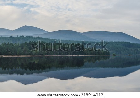Hill reflection in Loch Morlich, Scotland - stock photo