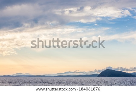 hills and mountains in the evening sun near the water sea bay at sunset in the clouds haze - stock photo