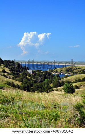 Hills of Nebraska grassland hide a beautiful Lake called McConaughy.  Blue sky is reflected in blue water.