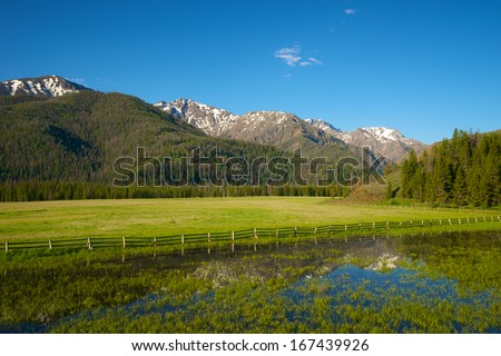 Hills, peaks, and ridges of the Rocky Mountains reflected in the water of a lake bordering a farm. - stock photo