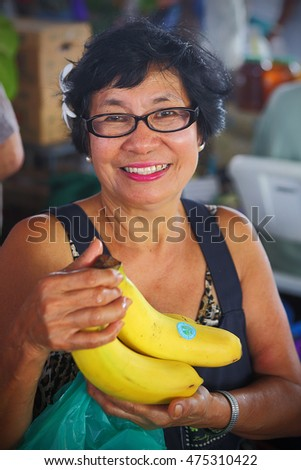 HILO, HAWAII - JUL 13, 2013: Unidentified woman with bananas at the Hilo farmers market on July 13, 2013. Every Wednesday, Hilo, Hawaii hosts a farmers market where locally grown produce is sold.