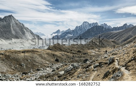 Himalayan guide on the trek to the background of the Gokyo glacier -  Nepal - stock photo
