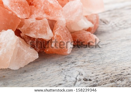 Himalayan pink crystal salt on wooden background