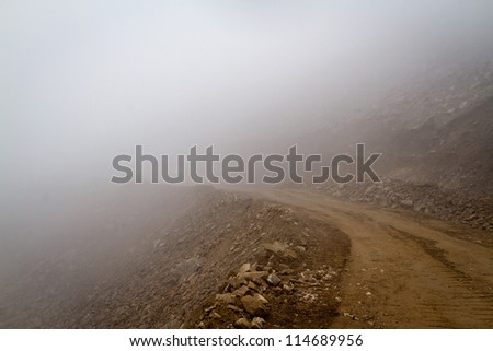 Himalayas. Gravel mountain road in the fog. - stock photo