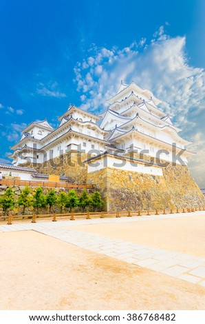 Himeji-jo castle on its high stone base and wide front courtyard on a clear, blue sky day in Himeji, Japan post 2015 renovations completed. Angled vertical copy space