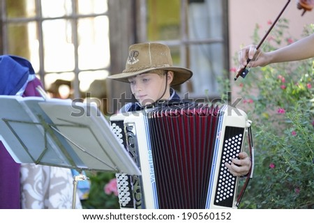 HIMEVILLE, SOUTH AFRICA - APRIL 26: Young musicians busking at a   morning country fair on April 26, 2014, in Himeville, a popular tourism destination,  Drakensberg, Kwazulu Natal, South Africa .  - stock photo