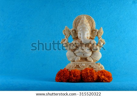 Hindu God Ganesha. Ganesha Idol on Blue Background with flowers.  - stock photo