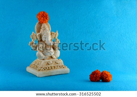 Hindu God Ganesha. Ganesha Idol on Blue Background with flowers.