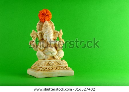 Hindu God Ganesha. Ganesha Idol on Green Background with flowers.