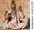 Hindu sadhu holy man, sits on the ghat, seeks alms on the street in Jaisalmer, Rajasthan, India . Close up - stock photo