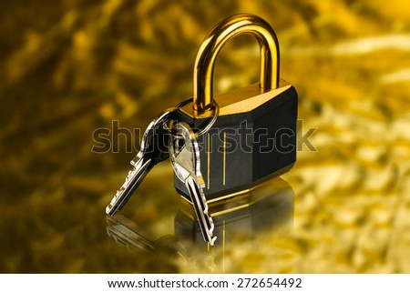 hinged lock with keys on golden background - stock photo