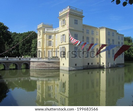 HINGENE, BELGIUM, JUNE 6 2014: The beautiful water surrounded d'Ursel Castle in Hingene. The castle provides the backdrop for the biennial 'Castle Festival' which attracts thousands of visitors. - stock photo